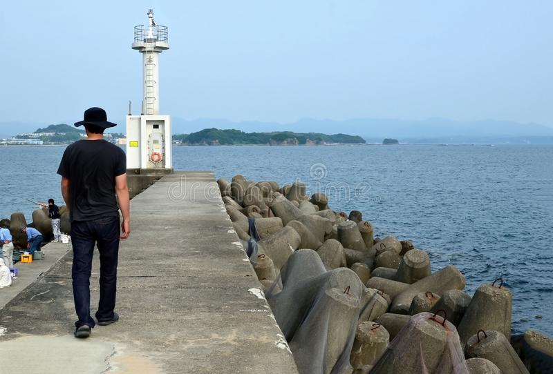 海和和歌山的灯塔和钓鱼者 库存图片