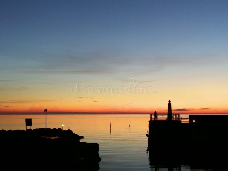 海和日落在小游艇船坞相接海湾在马尔摩瑞典 免版税图库摄影
