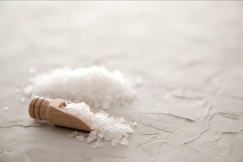 海在木瓢特写镜头的盐水晶在具体背景 有海盐的小铁锹 r 库存照片