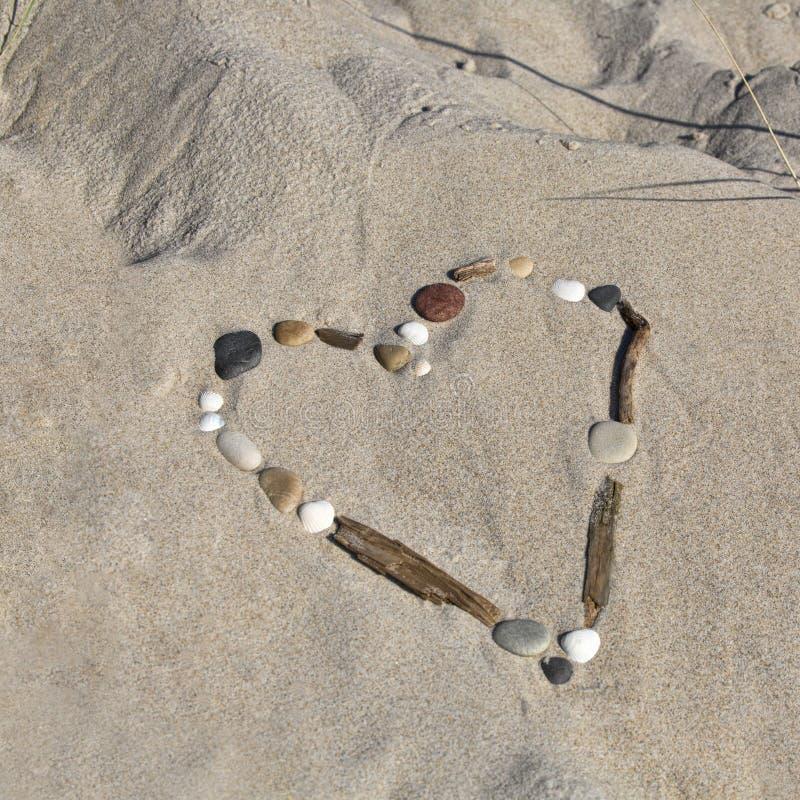 海壳和漂流木头的心脏在沙子 免版税图库摄影