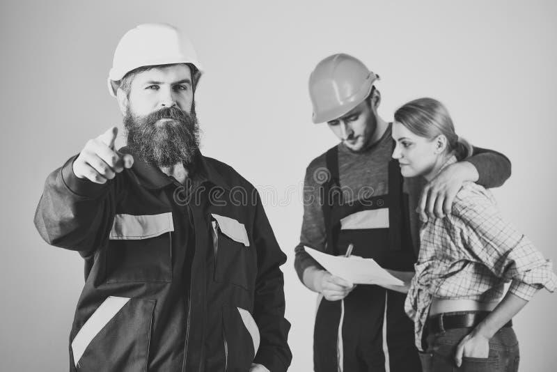 海外工作 补充概念 谈论工作者、建造者在盔甲的修理匠和的夫人旅团合同,灰色 免版税库存照片