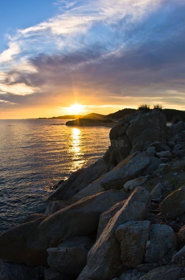 海岩石cloudscape的剪影和反射在日落的 图库摄影