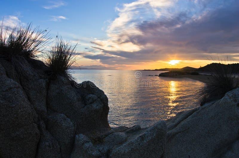 海岩石cloudscape的剪影和反射在日落的 库存照片