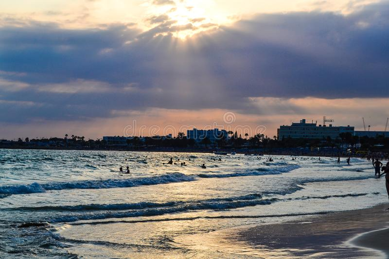 海岸在日落的晚上 由于云彩塞浦路斯,太阳` s光芒发光 ayia早餐塞浦路斯旅馆napa seaview 免版税库存图片