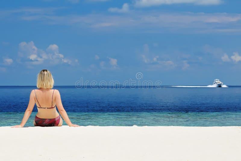 海岸坐的妇女年轻人 免版税库存照片