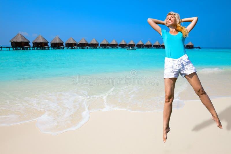 海岸女孩跳马尔代夫海洋 免版税库存图片