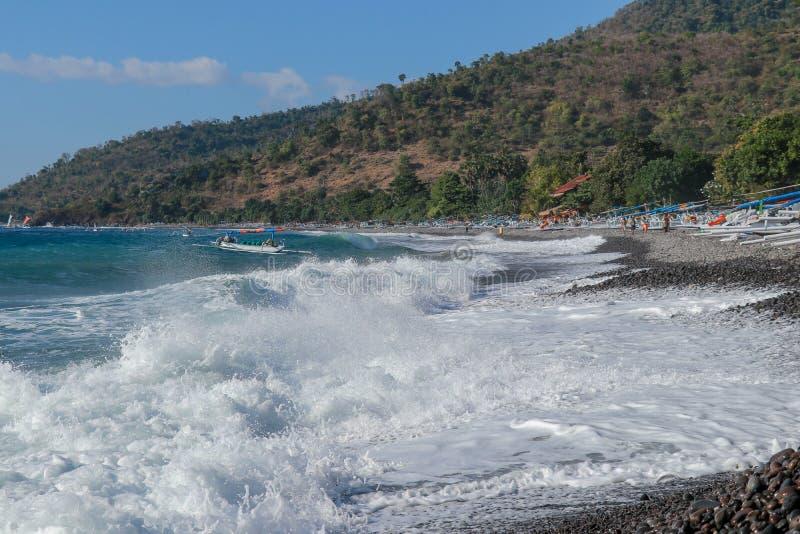 海岸断裂在巴厘岛,印度尼西亚攻击一个石海滩 在黑海滩的传统渔船 小船的一位渔夫 免版税图库摄影