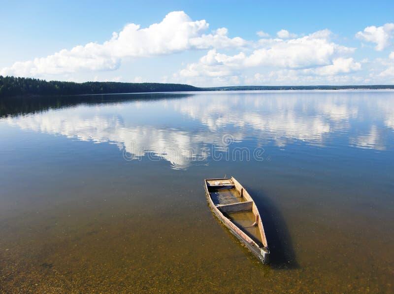 海岸水下的旧划船 云彩在水中被美丽地反射 被遗弃的破碎小手艺 库存图片