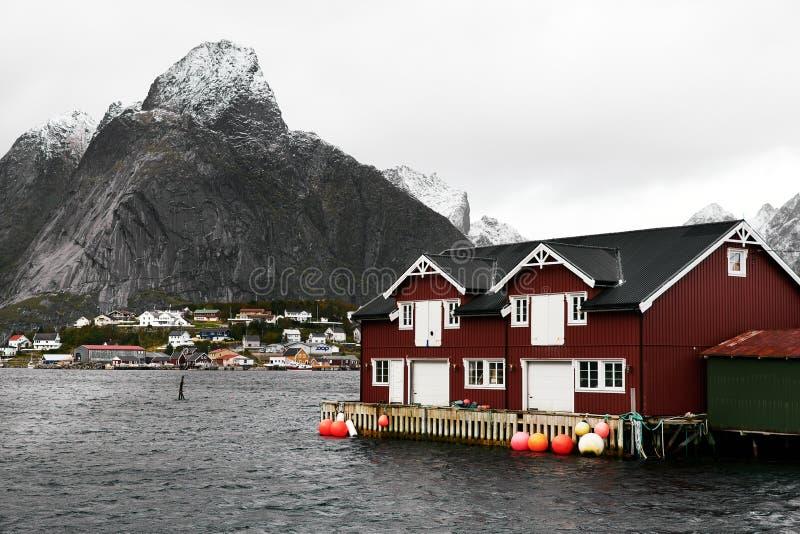海岸的传统红色木房子在一座积雪覆盖的山和另一个村庄前面的雷讷港口 库存图片