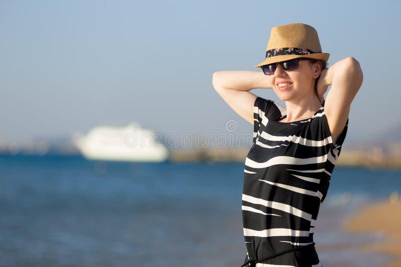 海岸的年轻无忧无虑的妇女 免版税库存照片