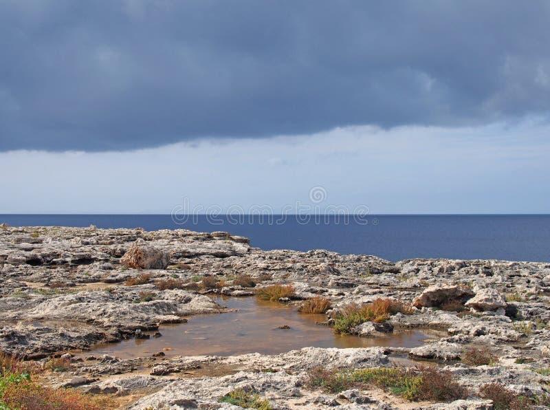 海岸线的风景看法与岩石水池的在与明亮的蓝色镇静夏天海和被日光照射了云彩的石灰石海滩边缘 免版税图库摄影