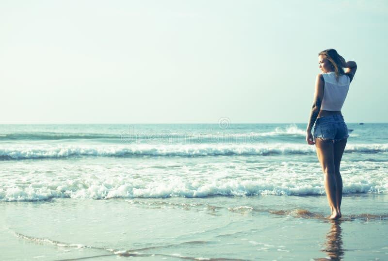 海岸走的放松的年轻俏丽的白肤金发的妇女,日落的,凉快的假期时尚夫人 免版税库存照片
