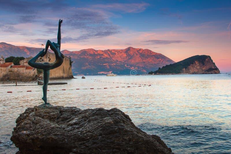 海岸风景:布德瓦老镇、舞女雕象, Sveti科列夫海岛和山在日落 黑山 图库摄影