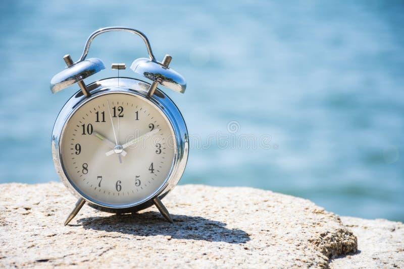 海底模糊自然石上的复古闹钟 免版税库存照片
