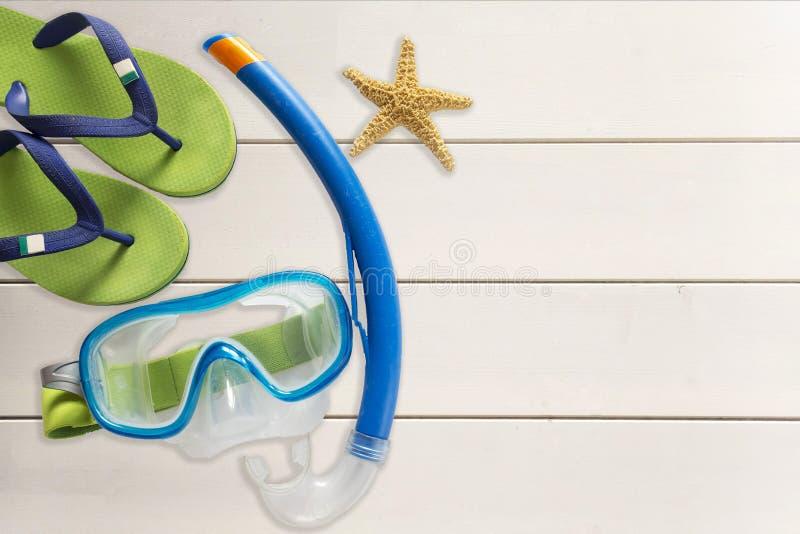 海拖鞋、水肺面具和海星在木背景 免版税库存照片