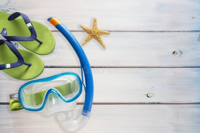 海拖鞋、水肺面具和海星在木背景 库存照片
