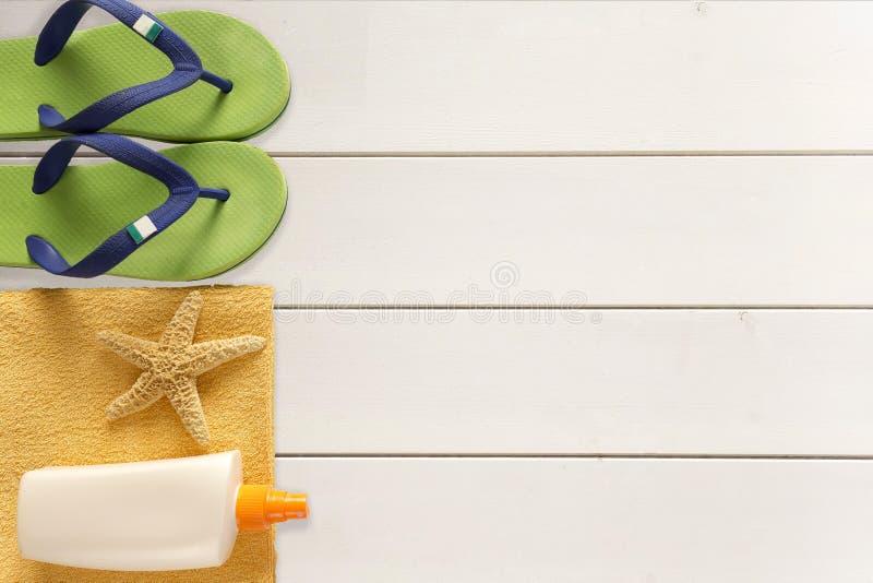 海拖鞋、遮光剂和毛巾在木背景 免版税图库摄影