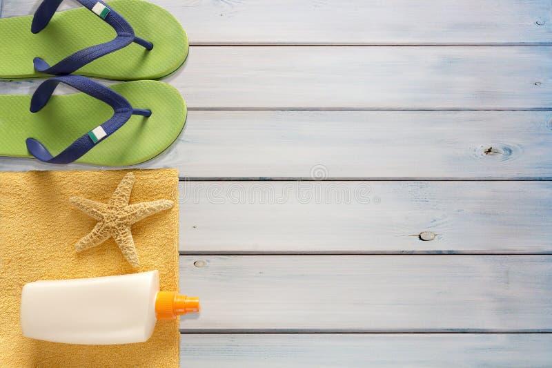 海拖鞋、遮光剂和毛巾在木背景 库存图片