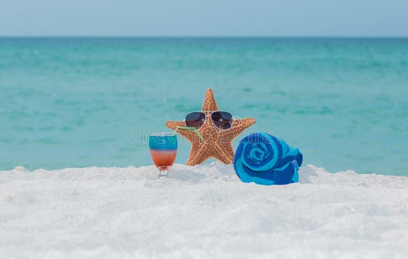 海星、毛巾和鸡尾酒在白色沙子热带海滩 免版税图库摄影