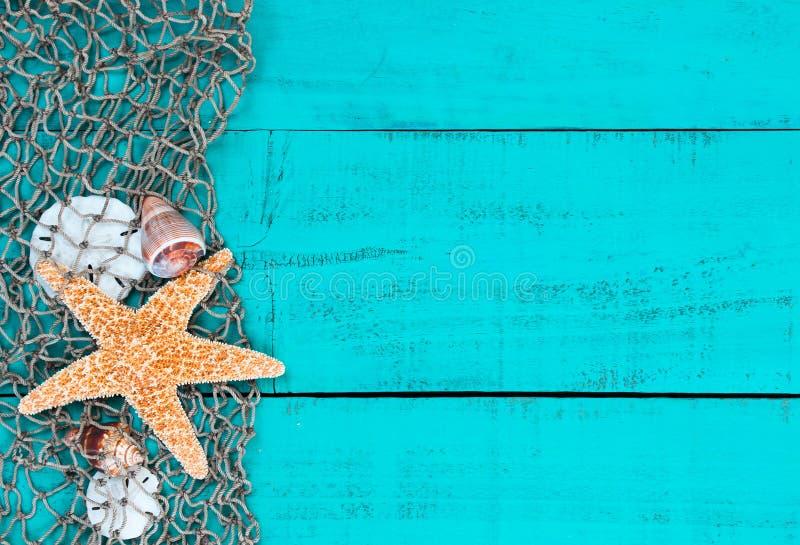 海星和壳在鱼网在小野鸭蓝色木标志 库存图片