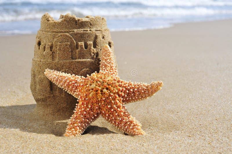海星和沙堡在海滩 免版税库存图片