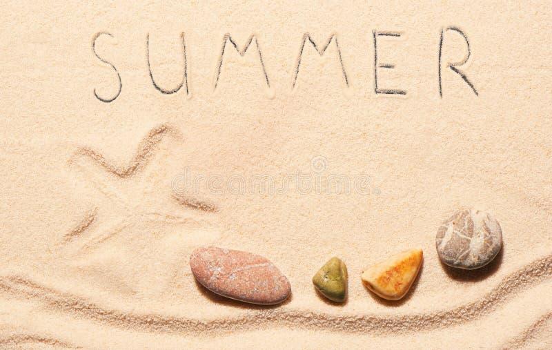 海星,海石头,在沙子得出的夏天字法标记  库存图片