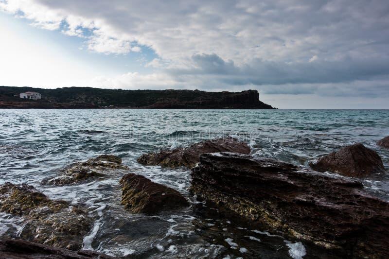 海晃动并且挥动在海滩在圣彼得罗海岛,撒丁岛 免版税库存照片