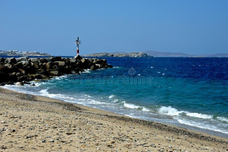 海景在从一个小卵石和沙滩看见的米科诺斯岛与码头用轻的设备 库存图片