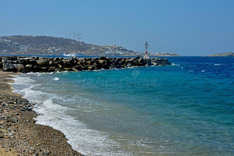 海景在从与码头的一小卵石bech看见的米科诺斯岛用轻的设备和一艘帆船 库存照片