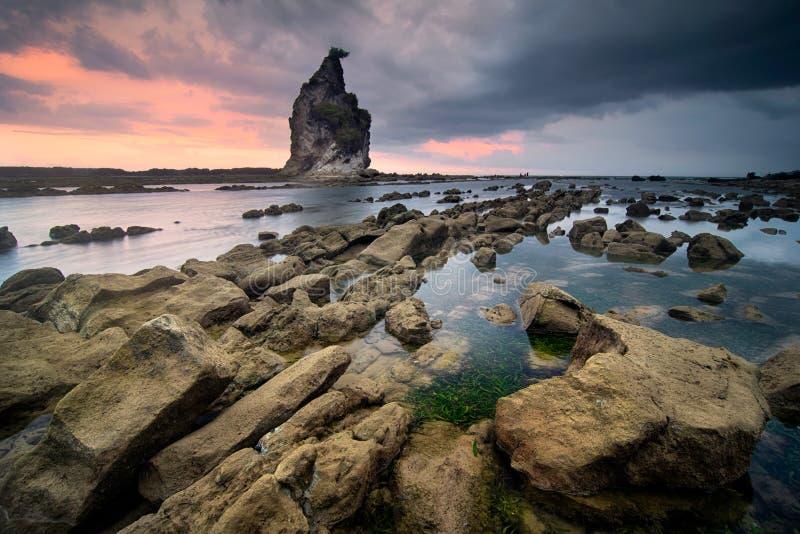 海景在Sawarna海滩,万丹省,印度尼西亚的日落风景 免版税库存照片