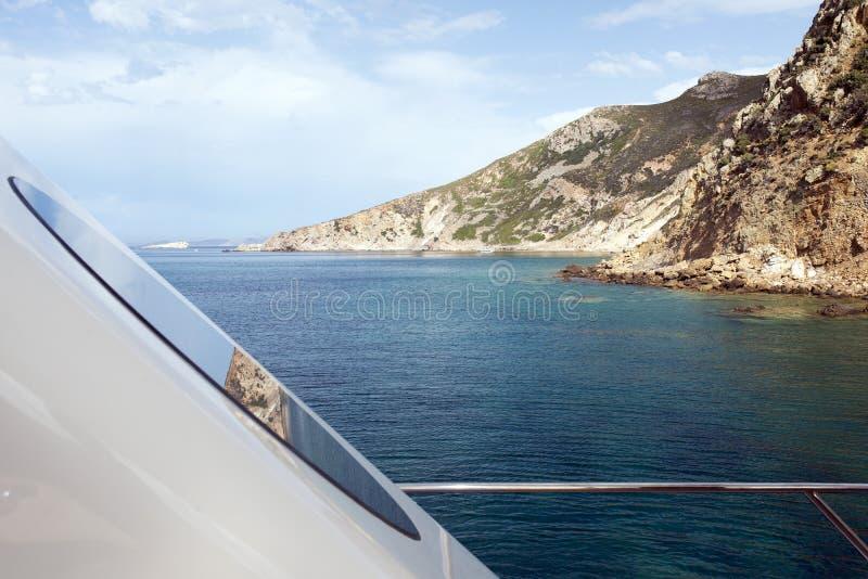 海景的看法和从汽艇的甲板的岩石风景和在小船的窗口的反射在夏天 免版税库存图片