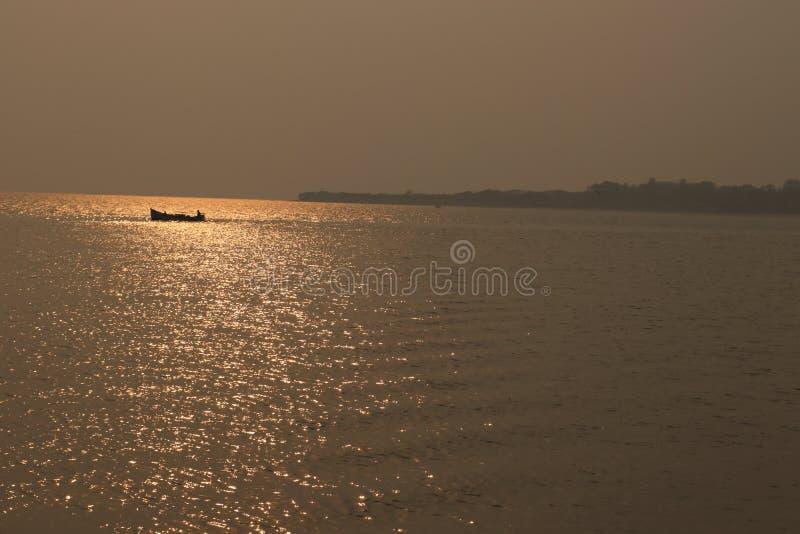 海景,有水手的偏僻的小船在美好的日落的风平浪静与太阳反射在水中 免版税图库摄影
