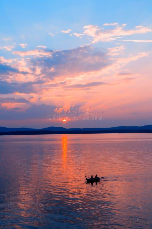 海晴朗的风景 阳光点燃的海 有不明身份的人的小船的,夏天海活动夏天晴朗的海 免版税库存照片