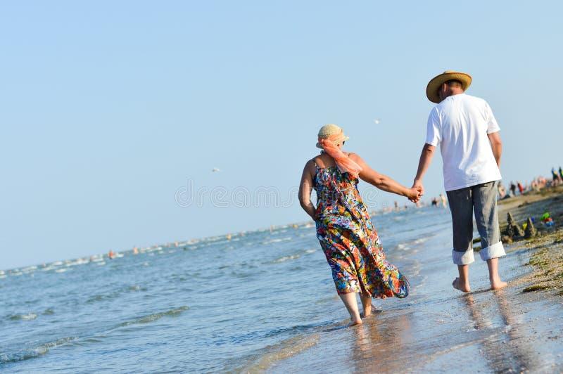海步行&愉快的成熟夫妇在海滨沙滩和举行手 免版税库存照片