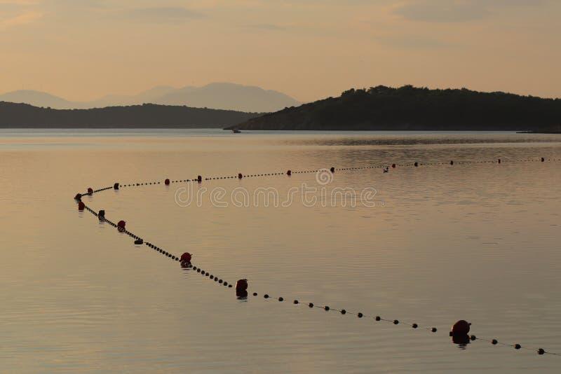 海水区域供沐浴假日游客使用操刀与安全的浮体 水的基于在清早 晒裂 免版税库存照片