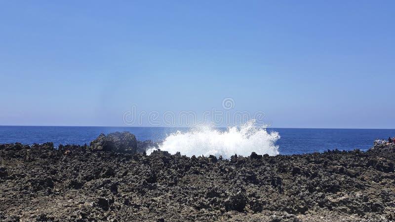 海水打反对岩石火山的裔 晴朗的日 n 库存图片