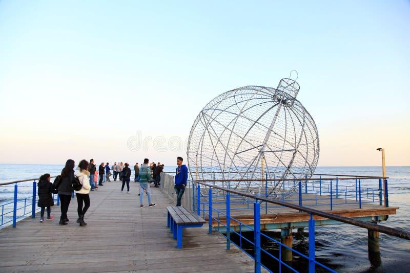 海江边的人们有巨型圣诞节球装饰的 免版税图库摄影