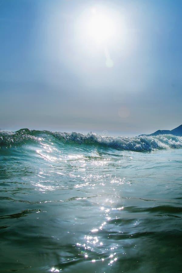 海波浪意想不到的看法在太阳光芒的作为手段和暑假的标志 库存照片