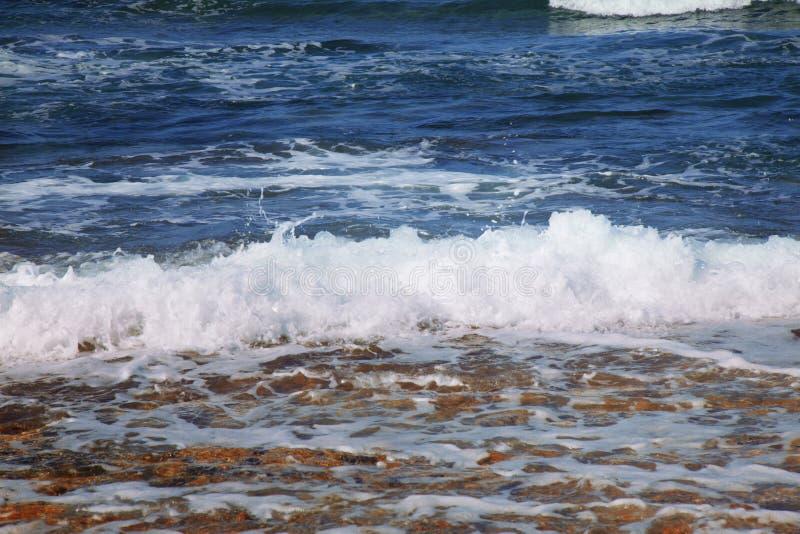 海波浪意想不到的看法在太阳光芒的作为手段的标志 夏天和假期 库存照片