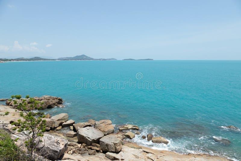 海波浪看法支持和在海岛和背景天空的意想不到的多岩石的海滩海岸与山,狂放的自然 热带土地 免版税库存图片