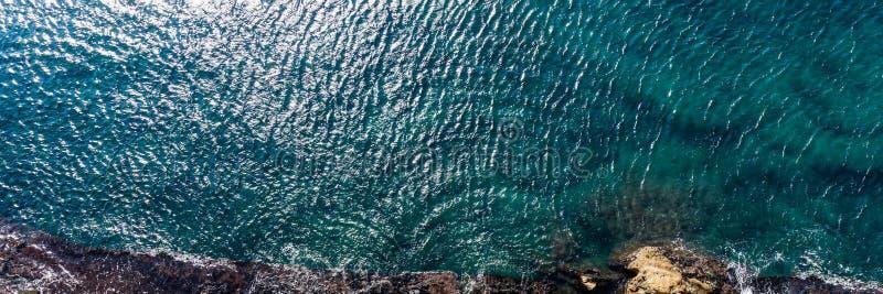 海波浪空中顶视图击中在岸的岩石与绿松石海水 免版税库存照片