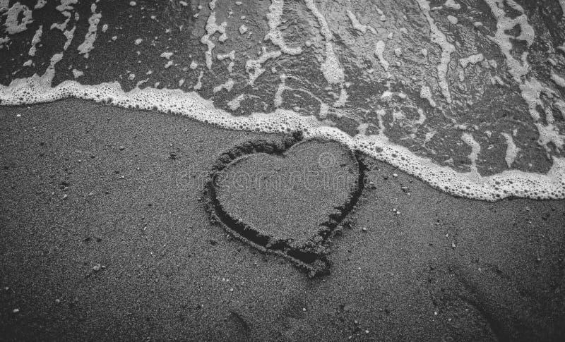 海波浪洗涤的去心脏单色照片在沙子画的 免版税库存图片