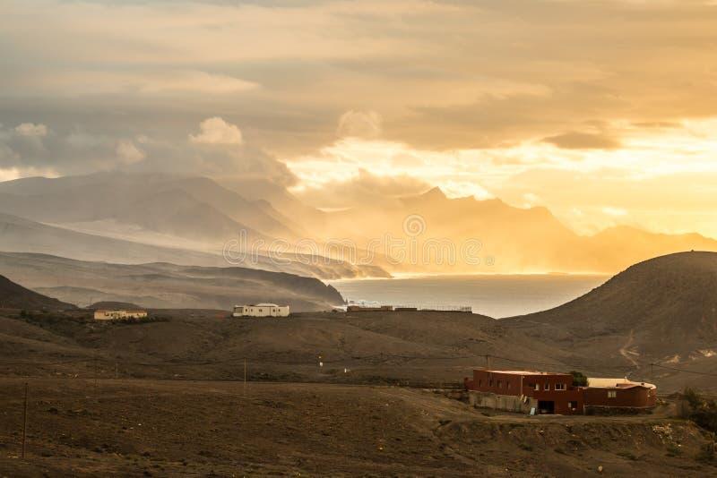海洋与多山海岸线和史诗轻的大气的日落风景 免版税库存照片