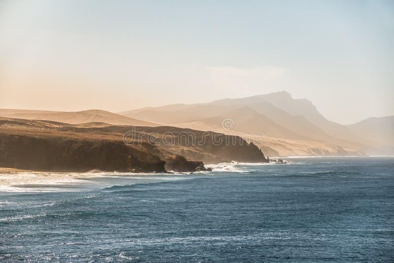 海洋与多山海岸线和蓝色海浪的日落风景 图库摄影