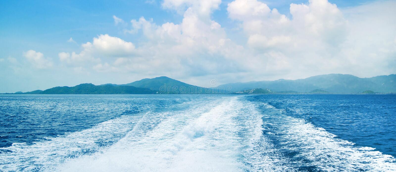 海洋和天空的看法与踪影在水 作为背景蓝色海运太有用的墙纸 库存图片