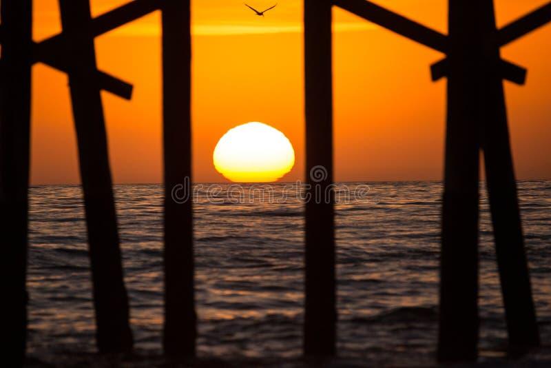 海洋在橙色日落西海岸期间的码头剪影 免版税图库摄影