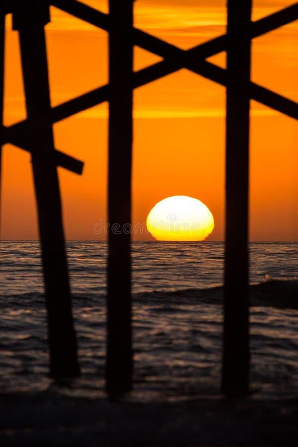 海洋在橙色日落西海岸期间的码头剪影 库存照片