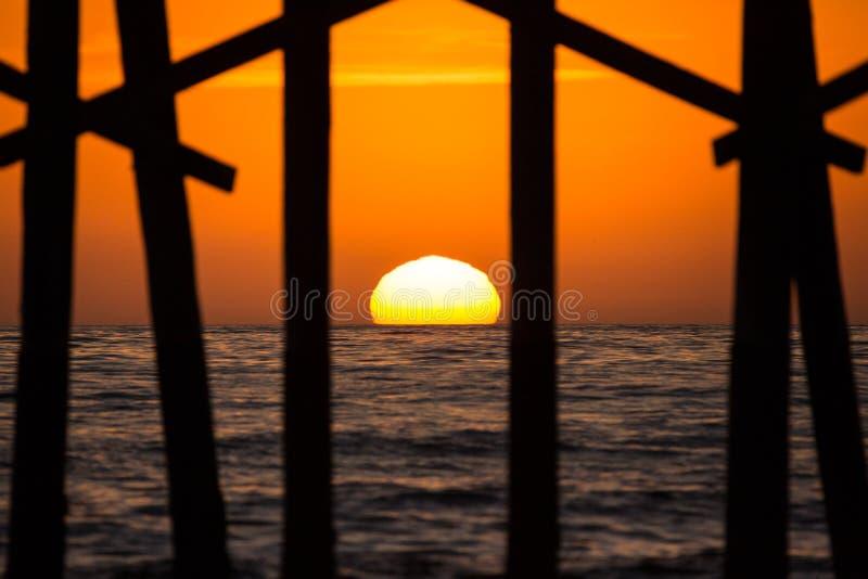 海洋在橙色日落西海岸期间的码头剪影 库存图片