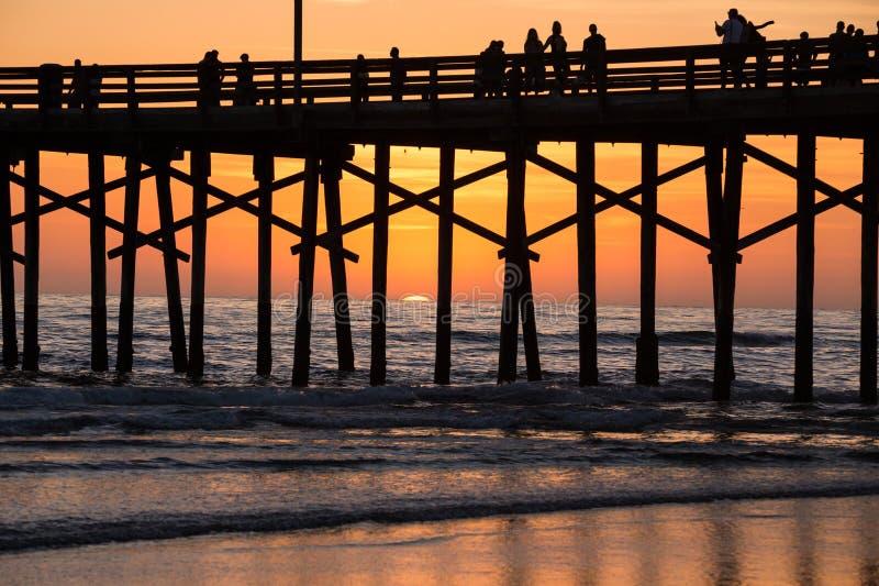 海洋在橙色日落西海岸期间的码头剪影 图库摄影