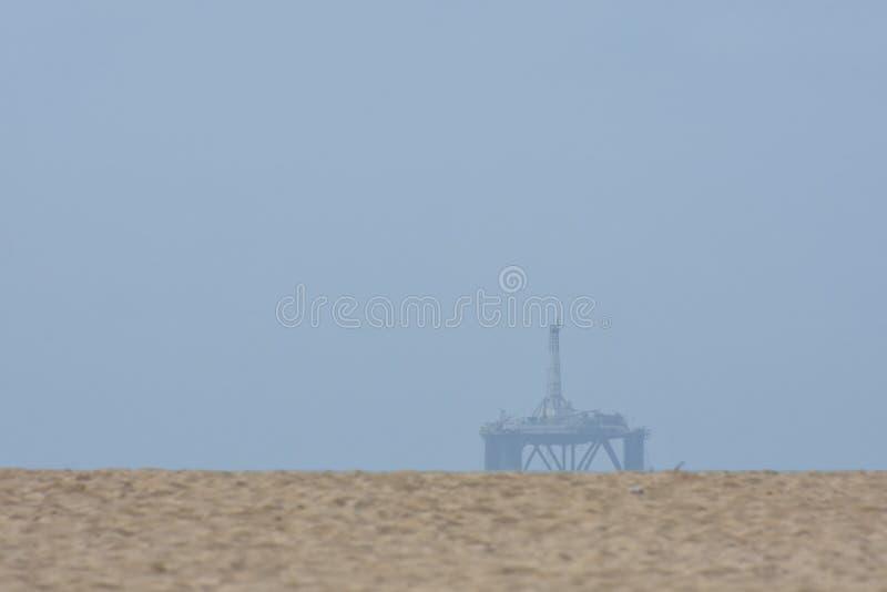 海洋在海滩沙丘的石油平台 库存照片